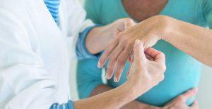 врач оценивает состояние руки пациента